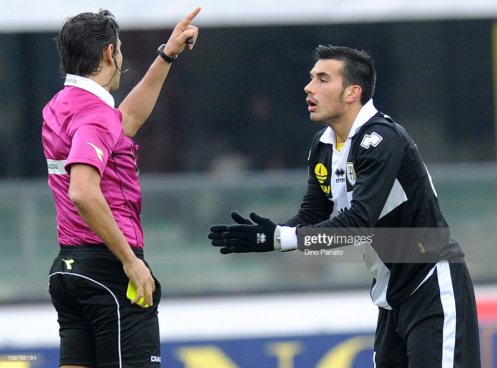 referee Gianpaolo Calvarese (L) show yellow card to Nicola Sansone of Parma FC during the Serie A match between AC Chievo Verona and Parma FC at Stadio Marc'Antonio Bentegodi on January 20, 2013 in Verona, Italy.