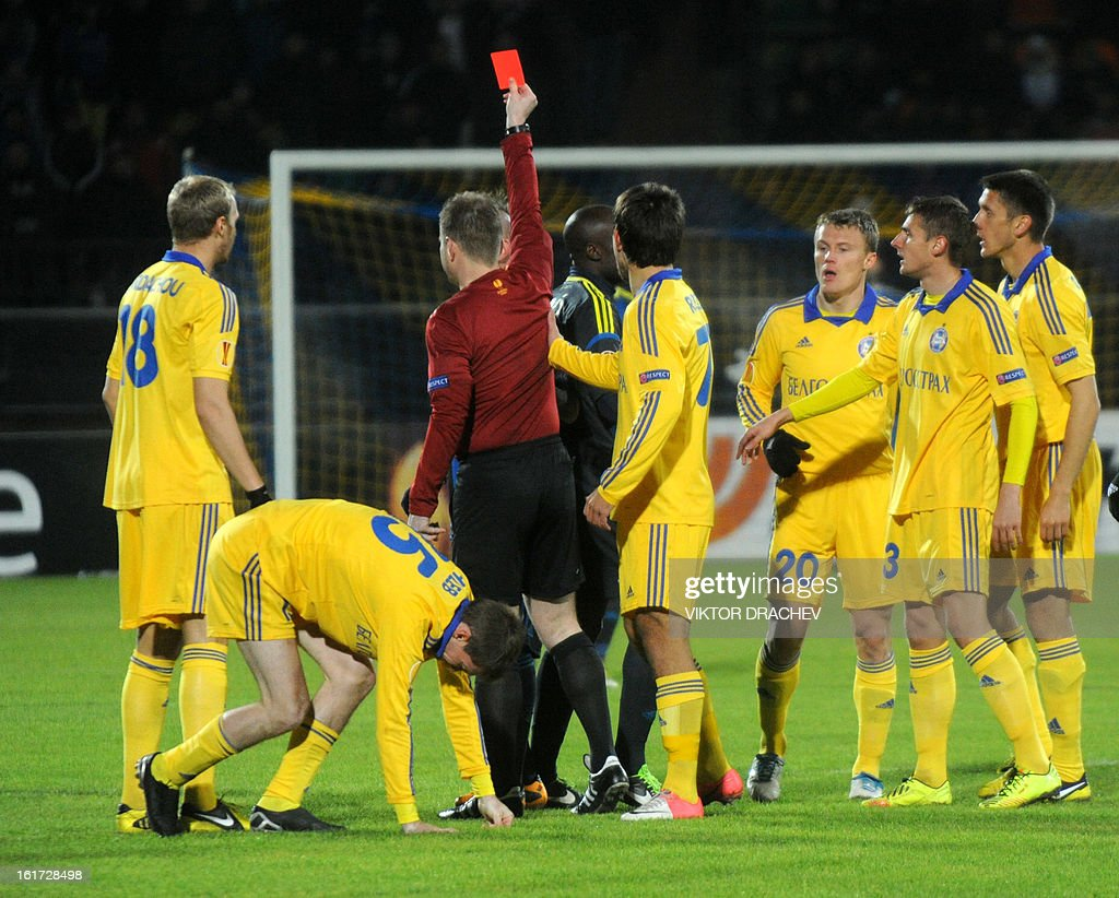 A referee (3rd L) gives a red cart to Fenerbahce SK's Pierre Webo (partly seen 4th L) during the round of 32 Europa League football match Fenerbahce SK against Bate Borisov at Neman Stadium in the Belarus town Grodno, some 300 km west of the capital Minsk on February 14, 2013.