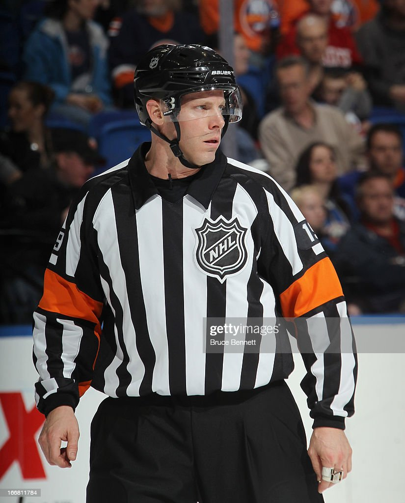 Referee Gord Dwyer #19 works the game between the New York Islanders and the Florida Panthers at the Nassau Veterans Memorial Coliseum on April 16, 2013 in Uniondale, New York. The Islanders defeated the Panthers 5-2.