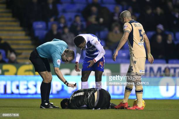 Referee Graham Scott and Nathaniel Chalobah check on Leeds United goalkeeper Marco Silvestri as Giuseppe Bellusci looks on