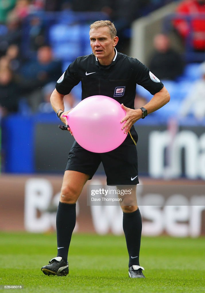 Referee Graham Scott bursts a balloon on the pitch during the Sky Bet Championship match between Bolton Wanderers and Hull City at the Macron Stadium on April 30, 2016 in Bolton, United Kingdom.