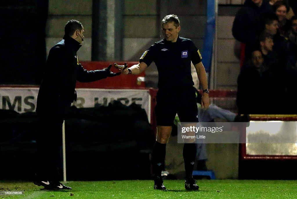 Referee Graham Scott removes a banana after being thrown on the pitch during the npower League Two match between AFC Wimbledon and Port Vale at The Cherry Red Records Stadium on January 24, 2013 in Kingston upon Thames, England.
