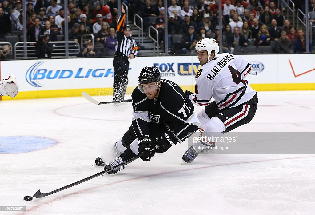NHL referee Greg Kimmerly #18 raises his arm to signal a penalty as <a gi-track='captionPersonalityLinkClicked' href=/galleries/search?phrase=Jeff+Carter&family=editorial&specificpeople=227320 ng-click='$event.stopPropagation()'>Jeff Carter</a> #77 of the Los Angeles Kings plays the puck away from <a gi-track='captionPersonalityLinkClicked' href=/galleries/search?phrase=Niklas+Hjalmarsson&family=editorial&specificpeople=2006442 ng-click='$event.stopPropagation()'>Niklas Hjalmarsson</a> #4 of the Chicago Blackhawks in the second period during the NHL game at Staples Center on February 3, 2014 in Los Angeles, California. Hjalmarsson was called for a hooking penalty. The Blackhawks defeated the Kings 5-3.
