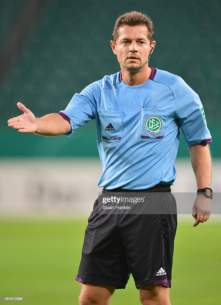 Referee Guenter Perl gestures during the second round DFB cup match between VfL Wolfsburg and Vfr Aalen at Volkswagen Arena on September 24, 2013 in Wolfsburg, Germany.