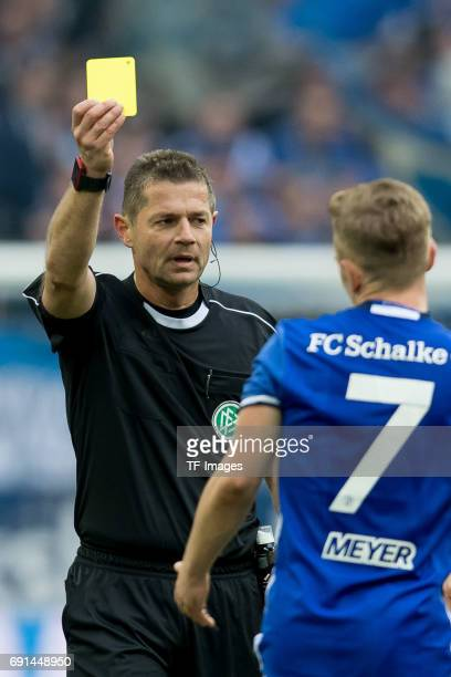 Referee Guenter Perl gives Max Meyer of Schalke the yellow card during the Bundesliga match between FC Schalke 04 and RB Leipzig at VeltinsArena on...
