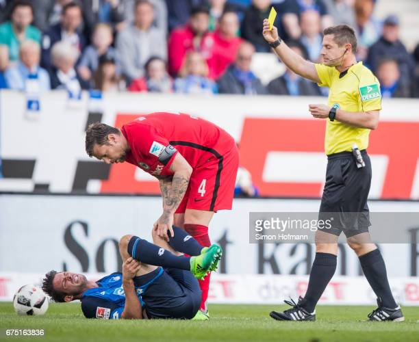 Referee Guenter Perl shows the yellow card to Marco Russ of Frankfurt during the Bundesliga match between TSG 1899 Hoffenheim and Eintracht Frankfurt...