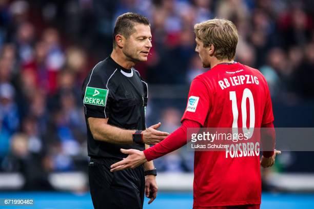Referee Guenter Perl talks to Emil Forsberg of Leipzig during the Bundesliga match between FC Schalke 04 and RB Leipzig at VeltinsArena on April 23...