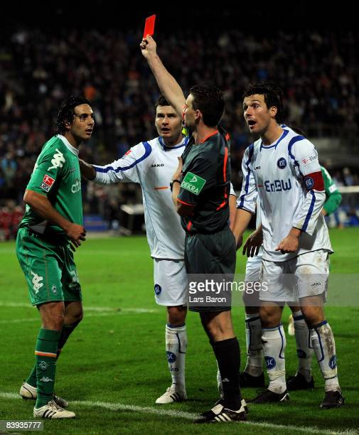 Referee Guido Winkmann shows Claudio Pizarro of Bremen the red card during the Bundesliga match between Karlsruher SC and Werder Bremen at the...