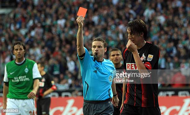 Referee Guido Winkmann shows Pedro Geromel of Koeln the red card after he stops the ball with the hand during the Bundesliga match between Werder...