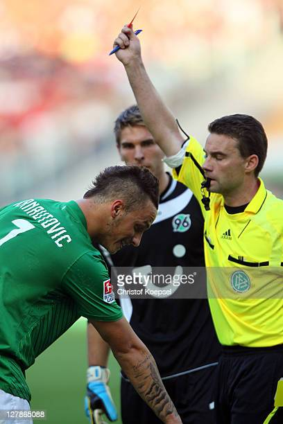 Referee Guido Winkmann shows the red card to Marko Arnautovic of Bremen during the Bundesliga match between Hanover 96 and SV Werder Bremen at AWD...