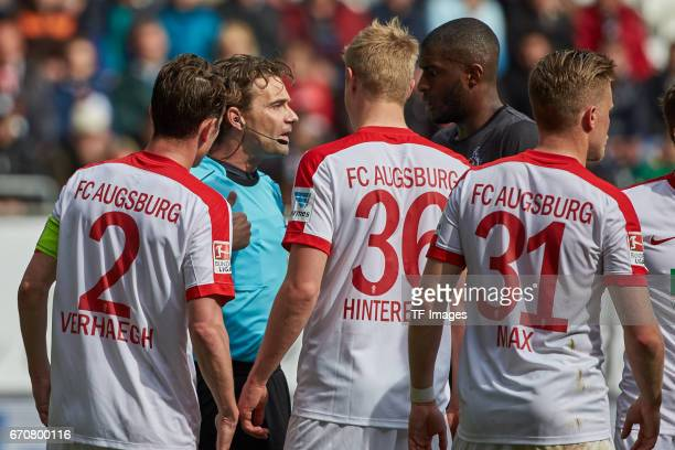 Referee Guido Winkmann speak with Paul Verhaegh of Augsburg Martin Hinteregger of Augsburg Anthony Modest and Philipp Max of Augsburg during the...
