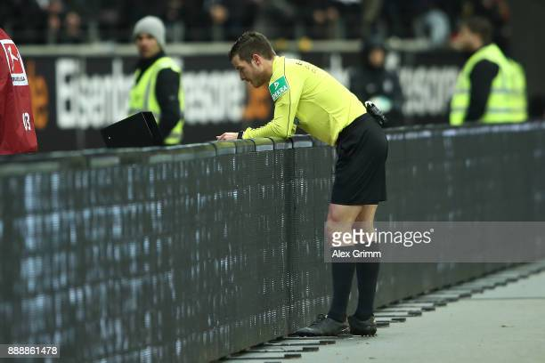 Referee Harm Osmers checks a decision for a red card to Marius Wolf of Frankfurt on the monitor which he later corrected into a yellow card during...