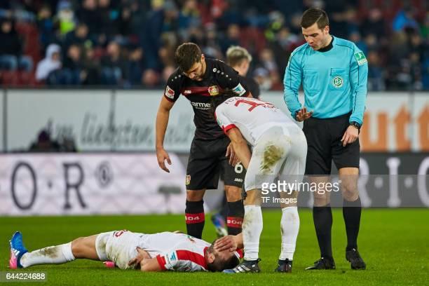 Referee Harm Osmers JaCheol Koo of Augsburg and Aleksandar Dragovic of Bayer Leverkusen and Raul Bobadilla of Augsburg looks on during the Bundesliga...