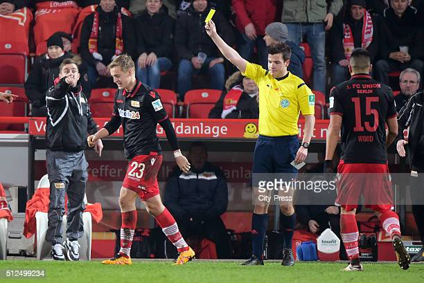 referee Harm Osmers shows Felix Kroos of 1 FC Union Berlin the yellow card during the game between Union Berlin and the Karlsruher SC on february 26...