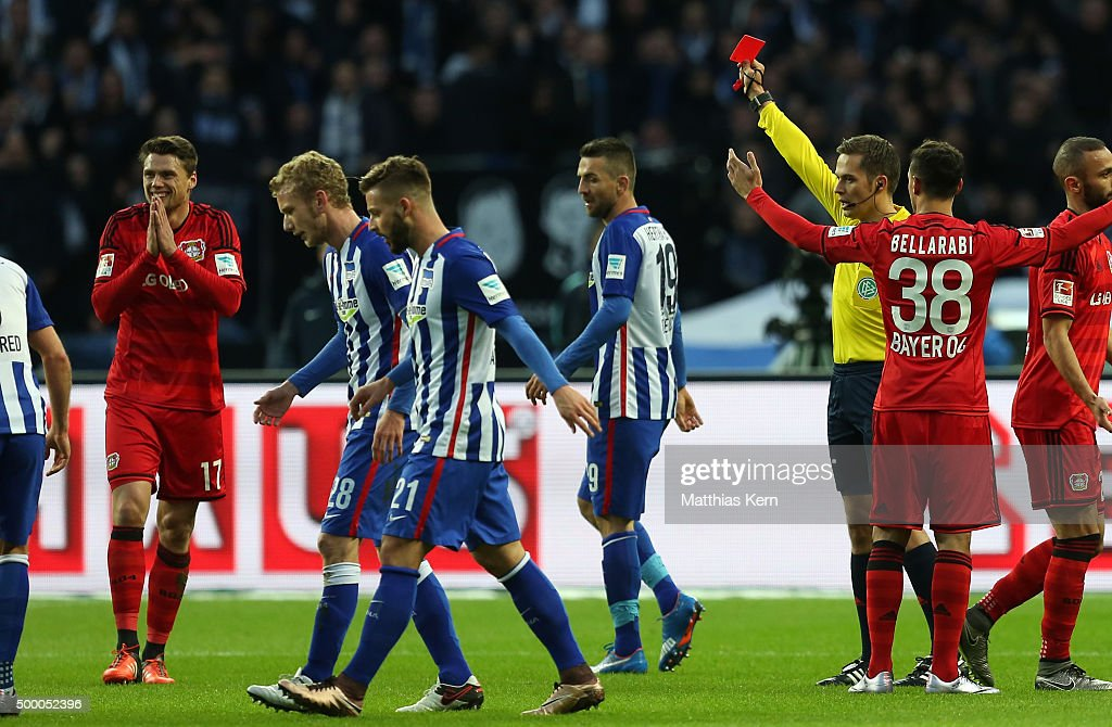 Referee Hartmann (R) shows the red card to <a gi-track='captionPersonalityLinkClicked' href=/galleries/search?phrase=Sebastian+Boenisch&family=editorial&specificpeople=632472 ng-click='$event.stopPropagation()'>Sebastian Boenisch</a> (L) during the Bundesliga match between Hertha BSC and Bayer Leverkusen at Olympiastadion on December 5, 2015 in Berlin, Germany.