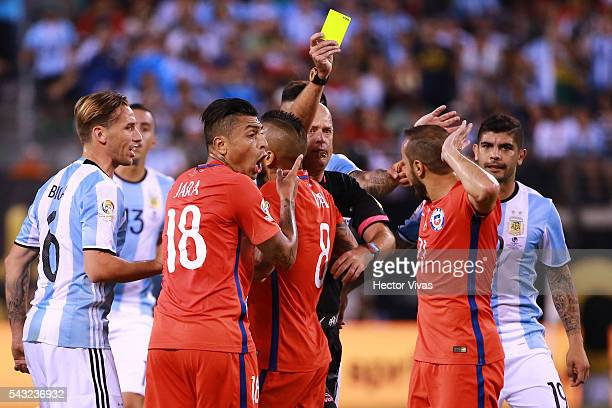 Referee Heber Lopes books Marcelo Diaz of Chile as teammate Gonzalo Jara reacts during the championship match between Argentina and Chile at MetLife...