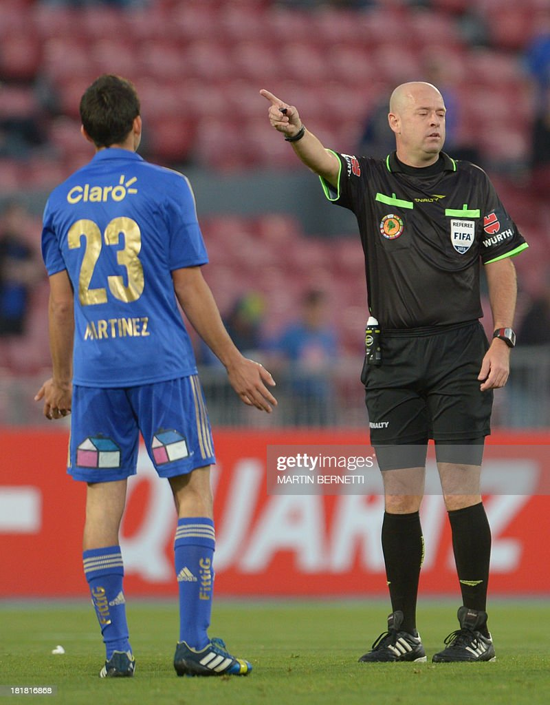 Referee Heber Lopes from Brazil gives instruction to Universidad de Chile's player Sebastian Martinez during their Copa Sudamericana 2013 football match against Lanus of Argentina at National stadium in Santiago, Chile, on September 25, 2013.