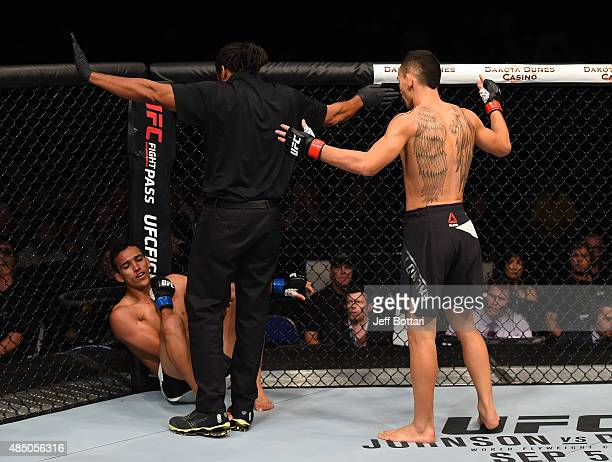 Referee Herb Dean calls a stop to the contest as Charles Oliveira of Brazil falls to the ground with an injury against Max Holloway of the United...