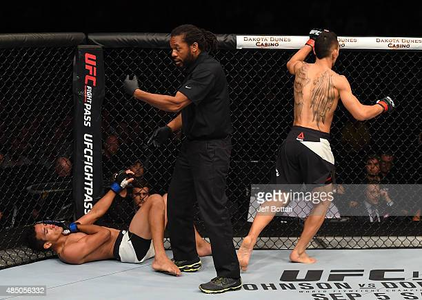 Referee Herb Dean calls for the doctor as Charles Oliveira of Brazil falls to the ground with an injury against Max Holloway of the United States in...