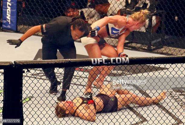 Referee Herb Dean ends the fight as New UFC women's bantamweight champion Holly Holm of the United States starts to celebrate her victory over Ronda...