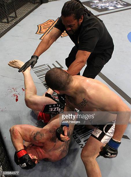Referee Herb Dean stops the fight as Cain Velasquez defeats Brock Lesnar in the first round during the heavyweight title bout during UFC 121 on...