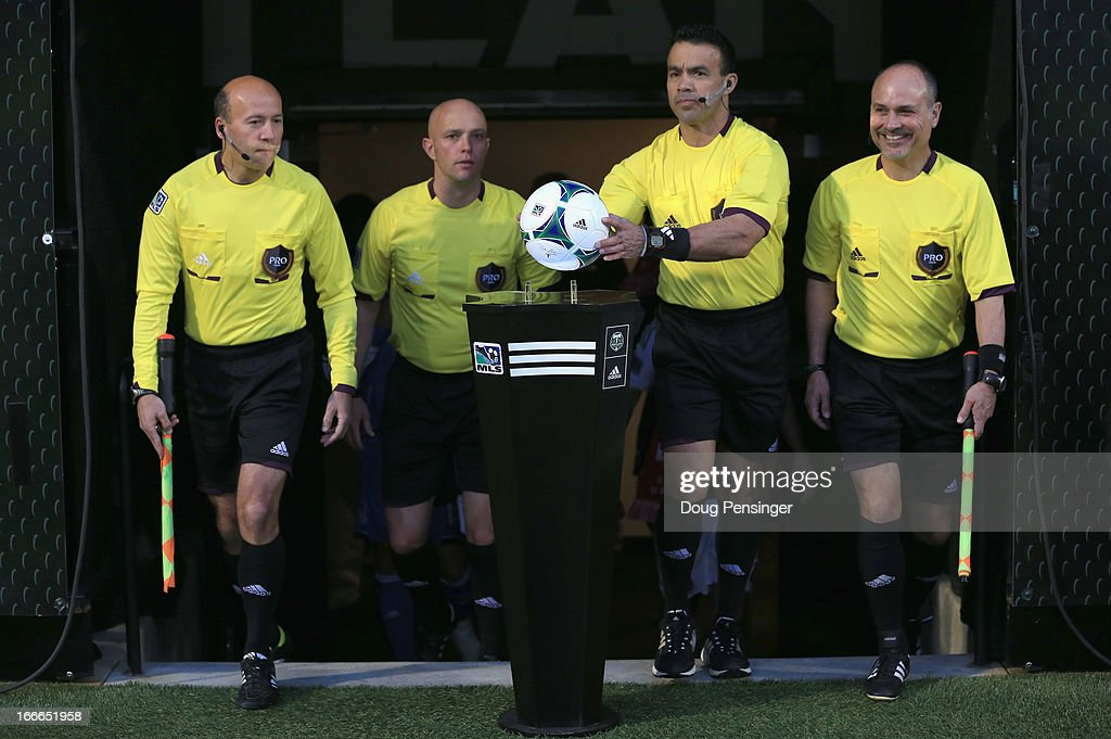 Referee Hilario Grajeda (2R) collects the game ball as his team takes the pitch to referee the match between the Portland Timbers and the San Jose Earthquakes at JELD-WEN Field on April 14, 2013 in Portland, Oregon. The Timbers defeated the Earthquakes 1-0.