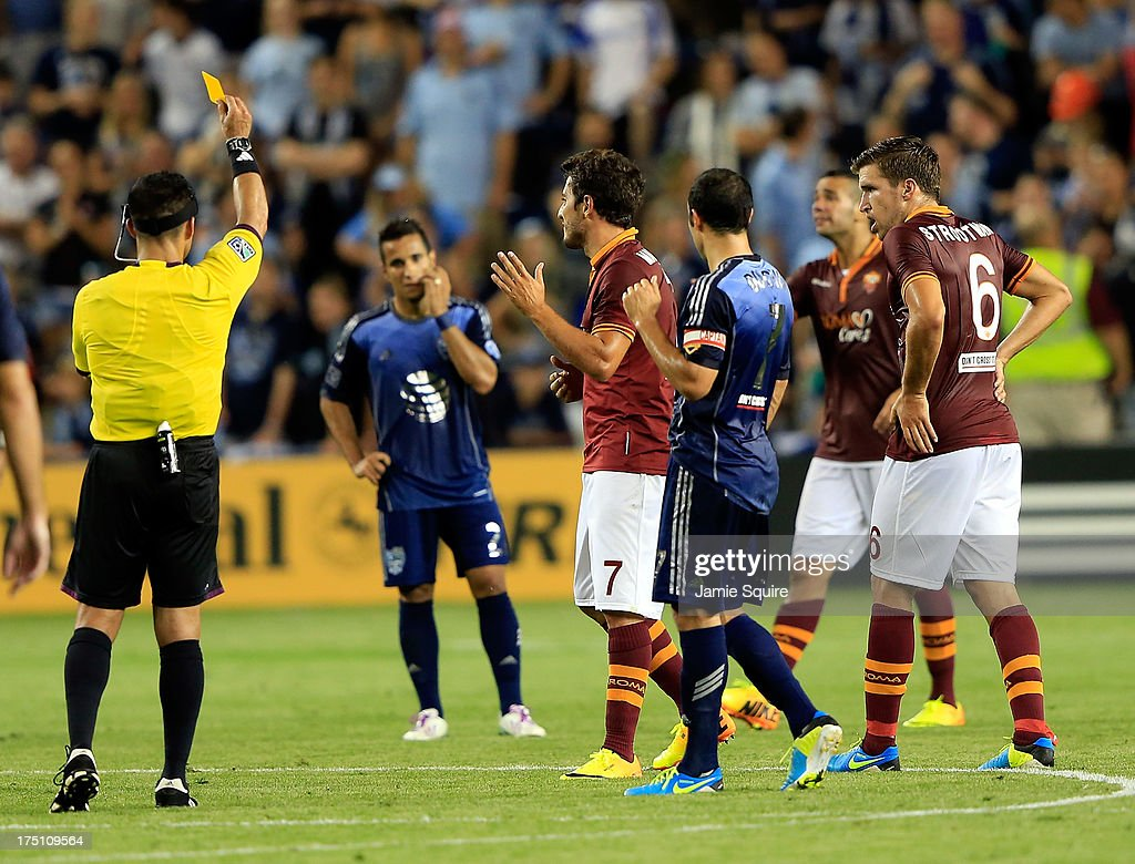 Referee Hilario Grajeda shows a yellow card to Marquinho #7 of AS Roma during the 2013 Major League Soccer All Star Game against the MLS All-Stars at Sporting Park on July 31, 2013 in Kansas City, Kansas.