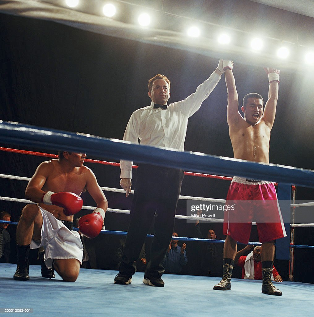 Referee holding up winning welterweight boxer's hand : Stock Photo