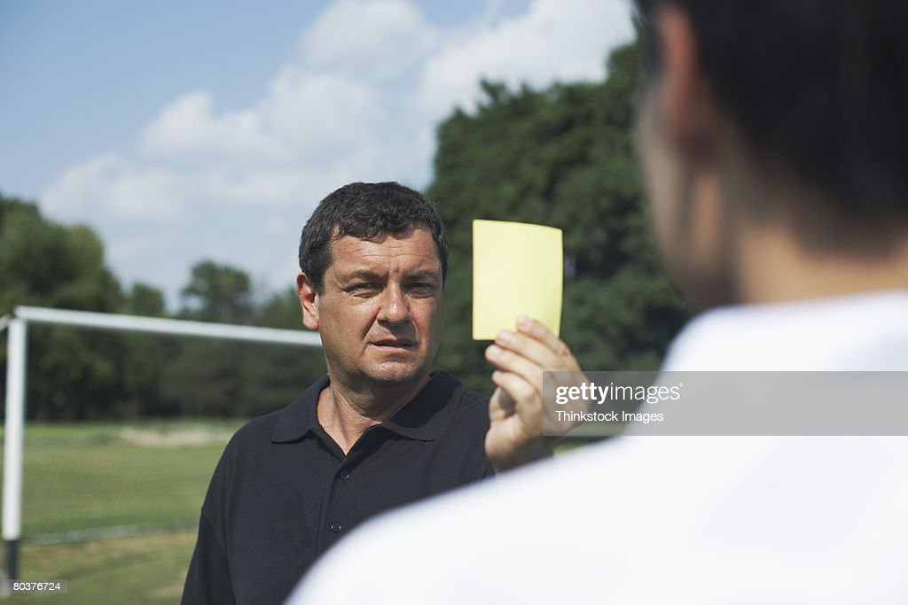Referee holding yellow card : Stock Photo