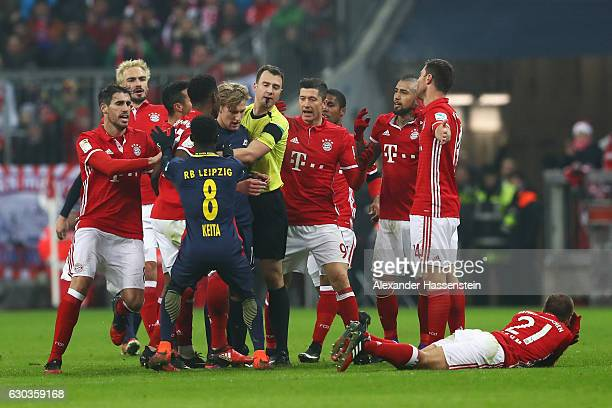 Referee holds back Emil Forsberg of RB Leipzig after he sent off during the Bundesliga match between Bayern Muenchen and RB Leipzig at Allianz Arena...
