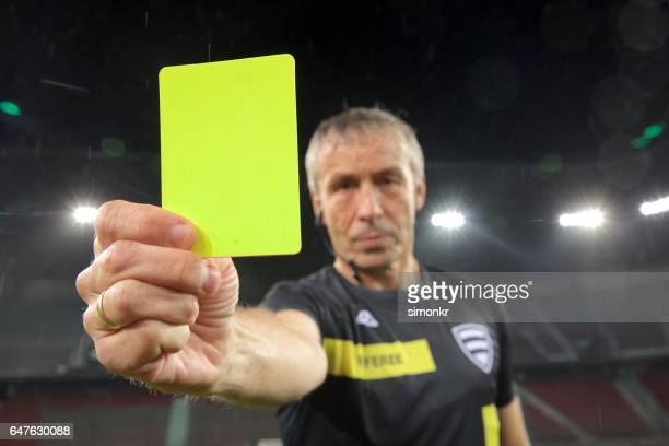 Referee holds up yellow card