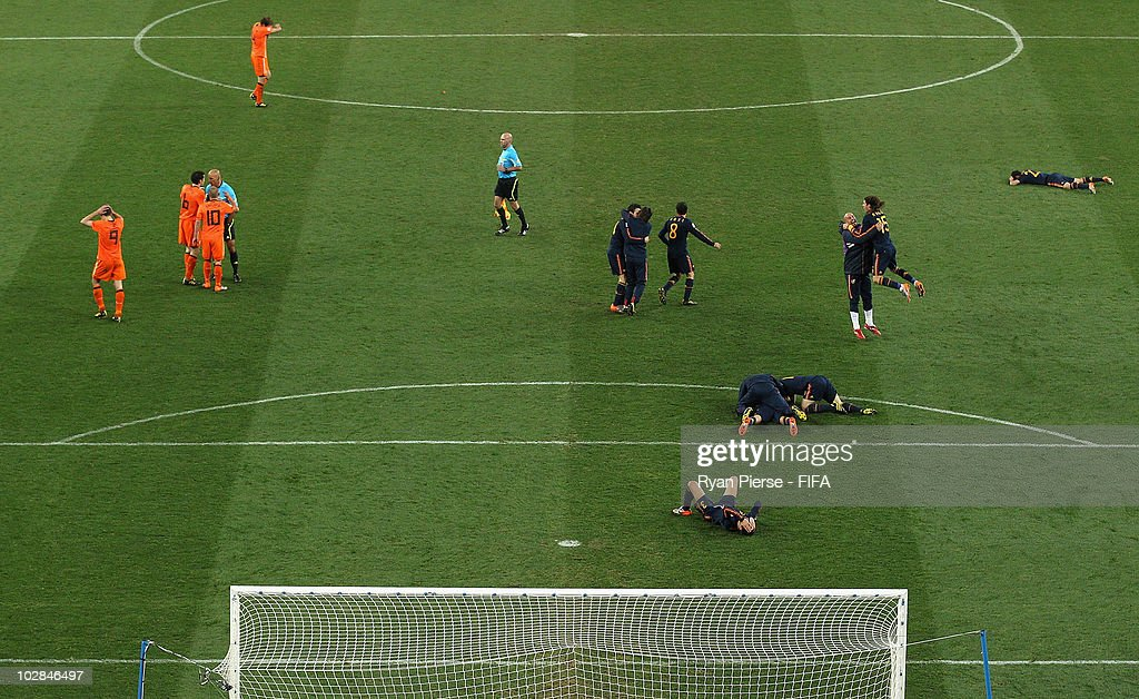 Referee Howard Webb blows the final whistle as the Spain team celebrate winning the World Cup and the Netherlands team look dejected during during the 2010 FIFA World Cup South Africa Final match between Netherlands and Spain at Soccer City Stadium on July 11, 2010 in Johannesburg, South Africa.