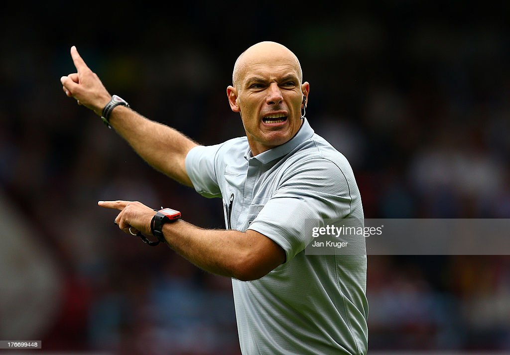 Referee <a gi-track='captionPersonalityLinkClicked' href=/galleries/search?phrase=Howard+Webb&family=editorial&specificpeople=647148 ng-click='$event.stopPropagation()'>Howard Webb</a> directs play during the Barclays Premier League match between West Ham United and Cardiff City at the Bolyen Ground on August 17, 2013 in London, England. Webb wears a watch which will alert him of a goal in connection with goal line technology.