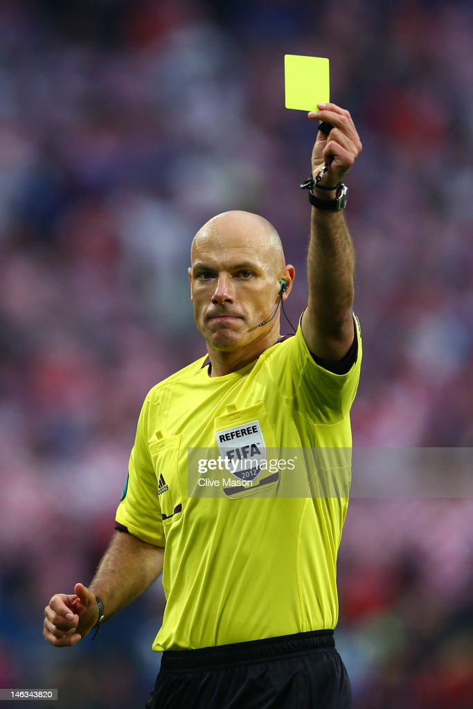 Referee Howard Webb issues a yellow card during the UEFA EURO 2012 group C match between Italy and Croatia at The Municipal Stadium on June 14, 2012 in Poznan, Poland.