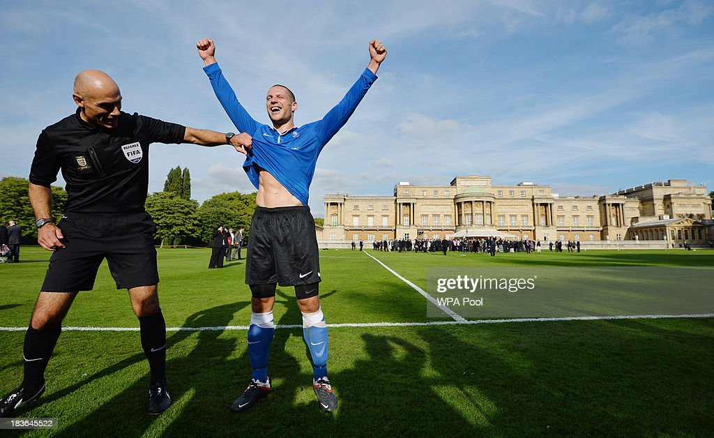 Referee Howard Webb (L) shares a joke with Polytechnic FC player Bojan Jelovac (R) as he celebrates scoring the first goal in the grounds of Buckingham Palace to mark the Football Association's 150th anniversary, on October 7, 2013 in London, England. The President of the Football Association, Prince William, Duke of Cambridge, will host the football match between Civil Service FC and Polytechnic FC, and will also host a reception to celebrate The FA's 150 grassroot heroes.