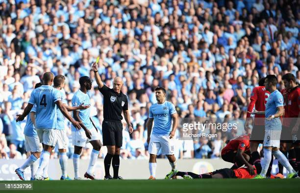 Referee Howard Webb shows a yellow card to Matija Nastasic of Manchester City during the Barclays Premier League match between Manchester City and...