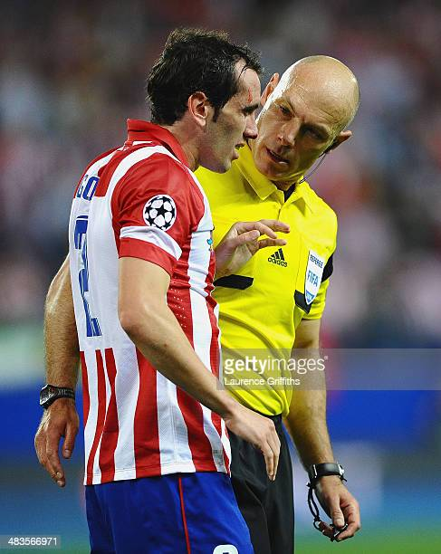 Referee Howard Webb talks to Diego Godin of Club Atletico de Madrid during the UEFA Champions League Quarter Final second leg match between Club...