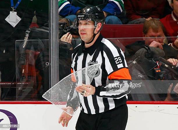 Referee Ian Walsh collects a broken piece if glass during the NHL game between the Vancouver Canucks and the Arizona Coyotes at Rogers Arena December...