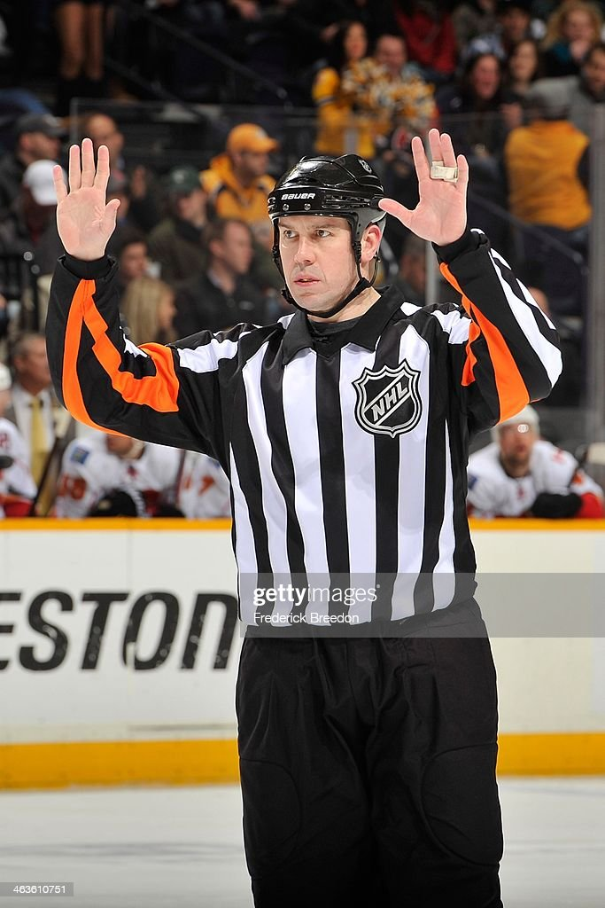 Referee Ian Walsh #29 officiates a game between the Calgary Flames and the Nashville Predators at Bridgestone Arena on January 14, 2014 in Nashville, Tennessee.