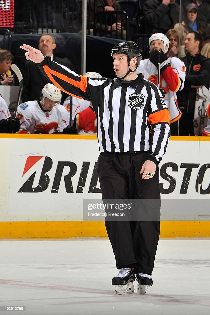 Referee Ian Walsh #29 officiates a game between the Nashville Predators and the Calgary Flames at Bridgestone Arena on January 14, 2014 in Nashville, Tennessee.