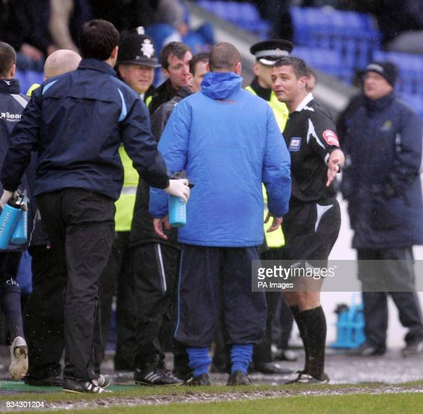 Referee Ian Williamson talks to Chester manager Simon Davies as he abandons the CocaCola League Two match due to the wet conditions at the Deva...