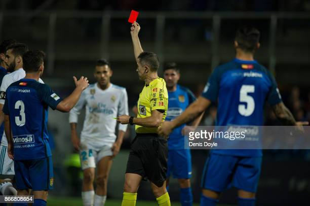 Referee Iglesias Villanueva shows the red card to Jesus Vallejo of Fuenlabrada during the Copa del Rey Round of 32 First Leg match between...