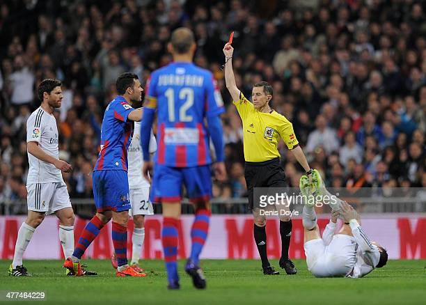 Referee Ignacio Iglesias Villanueva sends off David Navarro of Levante UD after he fouled Cristiano Ronaldo of Real Madrid CF during the La Liga...