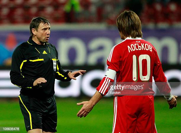 Referee Igor Egorov talks to Dmitri Loskov of FC Lokomotiv Moscow during the Russian Football League Championship match between FC Lokomotiv Moscow...