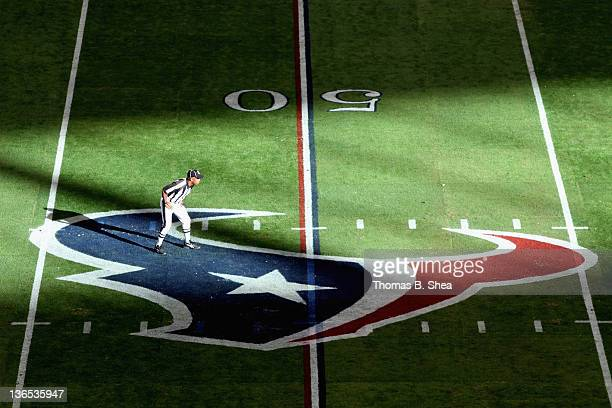 A referee is seen standing on a Houston Texans logo while the Texans host the Cincinnati Bengals during their 2012 AFC Wild Card Playoff game at...