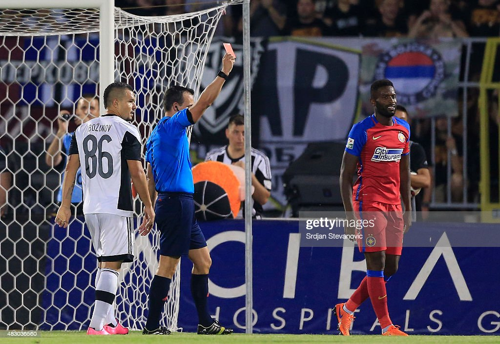 BELGRADE, SERBIA - AUGUST 05. Referee Istvan Vad (L) of Hungary shows the red card to the Fernando Varela (R) of FC Steaua Bucharest the UEFA Champions League Third Qualifying Round Second Leg match between FC Partizan Belgrade and FC Steaua Bucharest at FC Partizan stadium in Belgrade, Serbia on Wednesday, August 05, 2015.