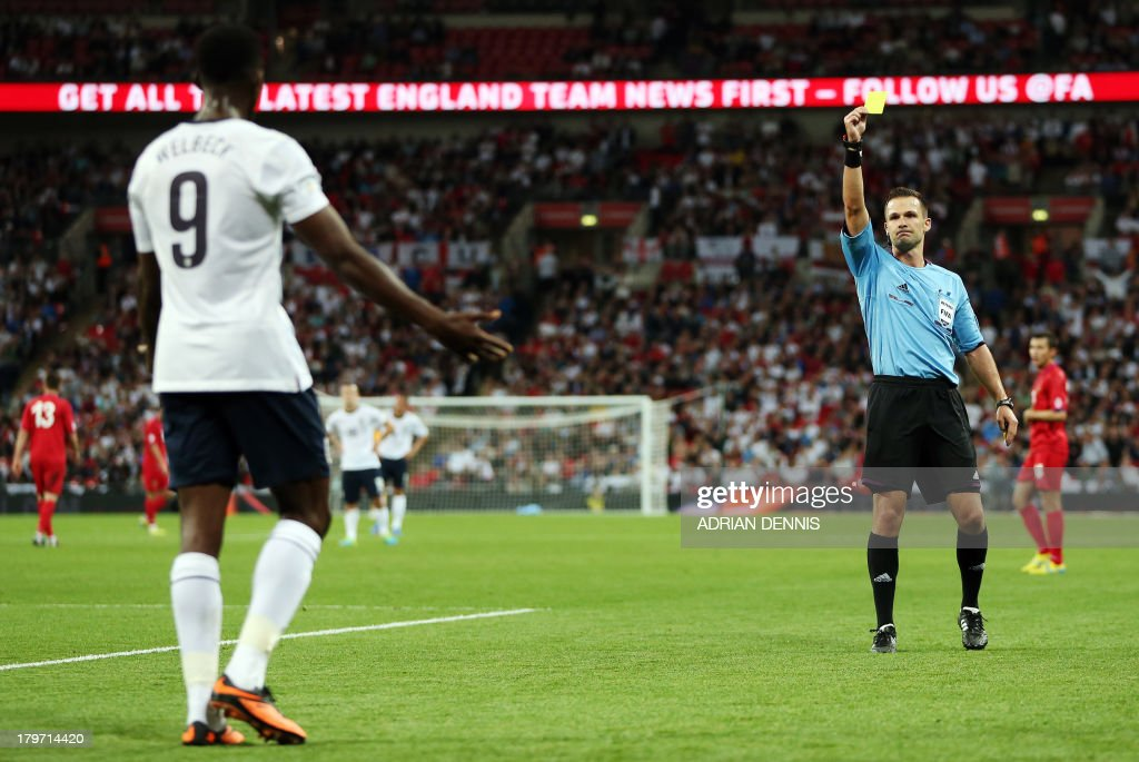 Referee Ivan Kruzliak (R) books England's Daniel Welbeck (L) against Moldova during the World Cup 2014 Group H qualifying football match between England and Moldova at Wembley Stadium in north London on September 6, 2013. England won the game 4-0.