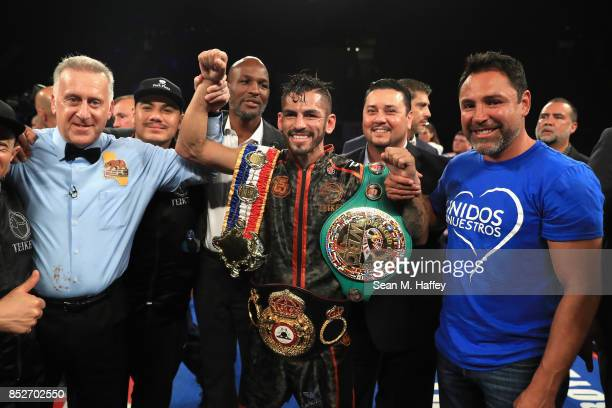 Referee Jack Reis Jorge Linares of Venezuela and Oscar De La Hoya look on celebrate the defeat by decision over Luke Campbell of Great Britain during...