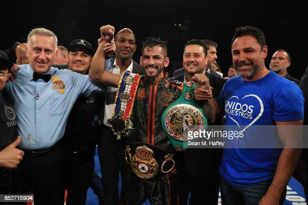 Referee Jack Reiss Jorge Linares of Venezuela and Oscar de la Hoya share a picture after Linares defeated by decision Luke Campbell in their WBA...