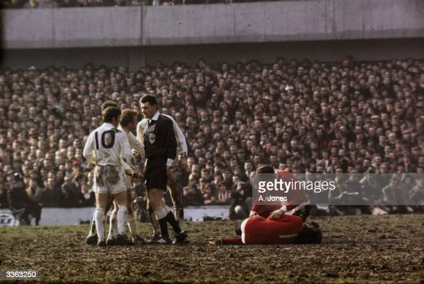 Referee Jack Taylor talks to Leeds United's Billy Bremner as Manchester United's Pat Crerand attends to injured team mate George Best